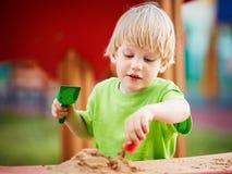 Piccolo ragazzo biondo che gioca sul campo da giuoco Fotografie Stock