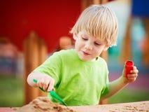 Piccolo ragazzo biondo che gioca sul campo da giuoco Immagini Stock