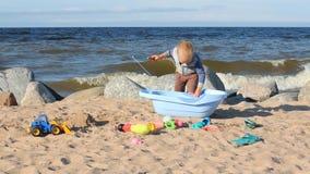 Piccolo ragazzo biondo che gioca sulla spiaggia stock footage