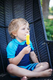 Piccolo ragazzo biondo che mangia il gelato giallo Fotografie Stock