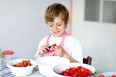Piccolo ragazzo biondo del bambino che aiuta e che produce l'inceppamento di fragola di estate Bacche di pulizia del bambino dive immagine stock