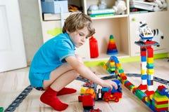 Piccolo ragazzo biondo del bambino che gioca con i blocchi di plastica variopinti e che crea stazione ferroviaria Immagine Stock Libera da Diritti