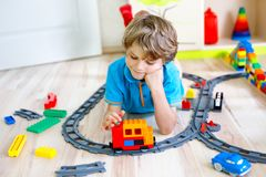 Piccolo ragazzo biondo del bambino che gioca con i blocchi di plastica variopinti e che crea stazione ferroviaria Immagini Stock
