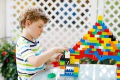 Piccolo ragazzo biondo del bambino e del bambino che gioca con i lotti dei blocchi di plastica variopinti Fotografia Stock Libera da Diritti