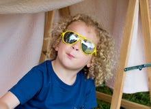 Piccolo ragazzo biondo ed occhiali da sole gialli Fotografie Stock Libere da Diritti