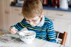 Piccolo ragazzo biondo felice del bambino che mangia i cereali per la prima colazione o il pranzo Cibo sano per i bambini Fotografie Stock Libere da Diritti