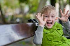 Piccolo ragazzo biondo felice emozionante con wow le mani aperte che esaminano macchina fotografica Fotografia Stock