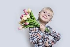 Piccolo ragazzo biondo sorridente che tiene un mazzo dei tulipani Ritratto su priorità bassa chiara immagine stock