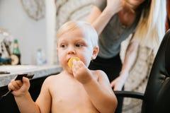 Piccolo ragazzo biondo sveglio adorabile prezioso del bambino che ostenta il suo nuovo stile di capelli dopo avere ottenuto il su immagini stock libere da diritti