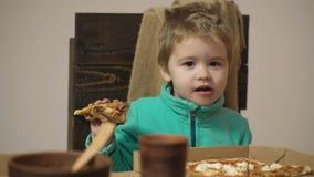 Piccolo ragazzo caucasico sveglio che mangia pizza Bambino affamato che prende un morso da pizza Ragazzino che ha fetta di pizza  video d archivio