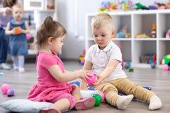 Piccolo ragazzo dei bambini e una ragazza che gioca insieme nella stanza della scuola materna Bambini in età prescolare in centro immagini stock libere da diritti