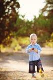 Piccolo ragazzo del bambino che cammina nel parco di estate all'aperto Immagine Stock