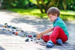 Piccolo ragazzo del bambino che gioca con il giocattolo dell'automobile Fotografia Stock