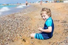 Piccolo ragazzo del bambino che gioca con la sabbia e le pietre sulla spiaggia Fotografia Stock Libera da Diritti