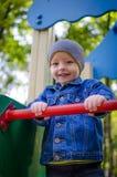 Piccolo ragazzo del bambino divertendosi ad un campo da giuoco Fotografia Stock