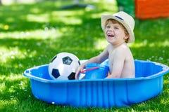 Piccolo ragazzo del bambino divertendosi con la spruzzatura dell'acqua nel luccio di estate Fotografie Stock