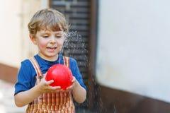 Piccolo ragazzo del bambino divertendosi con la spruzzatura dell'acqua nel luccio di estate Immagine Stock