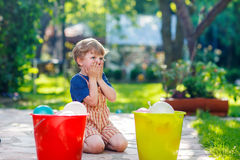 Piccolo ragazzo del bambino divertendosi con la spruzzatura dell'acqua nel luccio di estate Immagine Stock Libera da Diritti