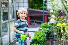 Piccolo ragazzo del bambino divertendosi con la spruzzatura dell'acqua nel luccio di estate Immagini Stock Libere da Diritti