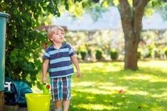 Piccolo ragazzo del bambino divertendosi con la spruzzatura dell'acqua nel luccio di estate Fotografia Stock