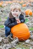 Piccolo ragazzo del bambino sul campo della toppa della zucca Fotografie Stock