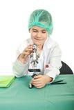 Piccolo ragazzo dell'allievo che per mezzo del microscopio Immagini Stock