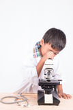 piccolo ragazzo dello studente che lavora con il microscopio Fotografia Stock Libera da Diritti
