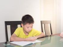 Piccolo ragazzo dello studente dell'Asia che studia e che fa il suo compito a casa Immagine Stock Libera da Diritti