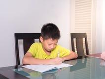 Piccolo ragazzo dello studente dell'Asia che studia e che fa il suo compito a casa Immagini Stock