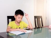 Piccolo ragazzo dello studente dell'Asia che studia e che fa il suo compito a casa Fotografia Stock Libera da Diritti