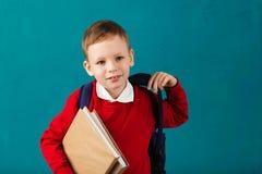 Piccolo ragazzo di scuola premuroso allegro in uniforme scolastico con il BAC Fotografie Stock