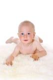 Piccolo ragazzo divertente che si trova sulla pancia e che sorride alla macchina fotografica Fotografie Stock