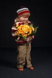 Piccolo ragazzo dolce con i fiori fotografia stock libera da diritti