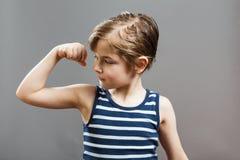Piccolo ragazzo duro allegro, mostrante i suoi muscoli Fotografie Stock Libere da Diritti