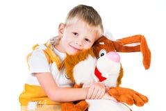 Piccolo ragazzo felice con il coniglio del giocattolo isolato su bianco Immagine Stock Libera da Diritti