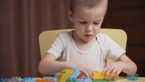 Piccolo ragazzo felice del metraggio che gioca con i blocchi colourful di costruttore a casa video d archivio
