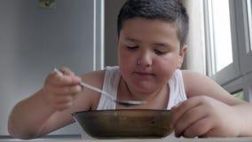 Piccolo ragazzo grasso sveglio che pranza nella cucina, mangiante un cucchiaio da tavola di minestra, obesità di infanzia di conc video d archivio