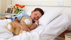 Piccolo ragazzo malato che dorme a letto con l'orsacchiotto video d archivio