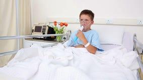 Piccolo ragazzo malato che si siede a letto con la maschera di ossigeno archivi video