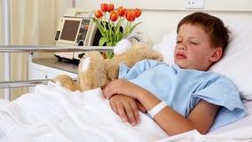 Piccolo ragazzo malato che si trova a letto con l'orsacchiotto stock footage