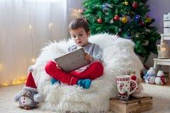 Piccolo ragazzo malato sveglio, sedendosi sulla borsa di fagiolo, giocante sulla compressa fotografia stock