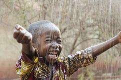 Piccolo ragazzo nero africano indigeno che sta all'aperto sotto l'acqua piovana per il simbolo dell'Africa fotografie stock