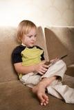 Piccolo ragazzo positivo con il calcolatore del ridurre in pani Fotografia Stock