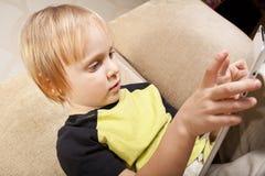 Piccolo ragazzo positivo con il calcolatore del ridurre in pani Immagini Stock Libere da Diritti