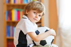 Piccolo ragazzo prescolare biondo del bambino con il gioco di sorveglianza della tazza di calcio di calcio della palla sulla TV F fotografia stock libera da diritti