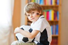 Piccolo ragazzo prescolare biondo del bambino con il gioco di sorveglianza della tazza di calcio di calcio della palla sulla TV F fotografie stock