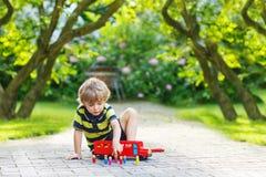 Piccolo ragazzo prescolare che gioca con il giocattolo dell'automobile Fotografia Stock