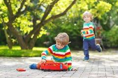 Piccolo ragazzo prescolare che gioca con il giocattolo dell'automobile Immagini Stock