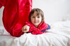 Piccolo ragazzo prescolare dolce, giocante supereroe a casa immagini stock libere da diritti