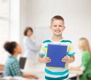 Piccolo ragazzo sorridente dello studente con il libro blu Immagini Stock Libere da Diritti